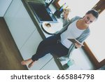 beautiful young woman using a... | Shutterstock . vector #665884798
