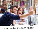 two friends taking a photo in... | Shutterstock . vector #666120430