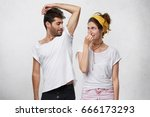Small photo of Female having disgusted look covering her nose with hand while smelling her husband`s armpit. Bearded man having nasty smell from sweat after running showing his wet underarm. Unpleasant smell