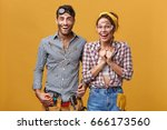 Attractive man and woman maintenance workers, technicians, electricians, plumbers or mechanics cheering, feeling happy and excited after got promoted. Postitive human facial expressions and emotions - stock photo