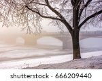 foggy morning near the bridge through the frozen river. tree in hoarfrost on the snowy embankment. gorgeous cityscape sunrise - stock photo