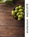 Small photo of Green olives in a ceramic bowl on a wooden background. Background with green olives. Olives. Copyspace. Green olives and branch of bay leaf. Bay leaf. Copyspace
