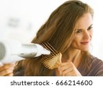 happy woman brushing and blow... | Shutterstock . vector #666214600