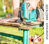 man sawing plank in park with... | Shutterstock . vector #666276100