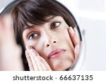 Woman Looking At Herself In The Mirror - stock photo