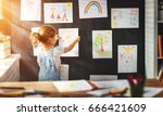 child girl hanging her drawings ... | Shutterstock . vector #666421609