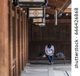 Small photo of TOKYO, JAPAN - 25TH JUNE 2017. Man reading at Meiji Jingu temple grounds. Meiji Jingu is a Shinto shrine dedicated to the deified spirits of Emperor Meiji and his spouse.