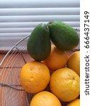 avocado. oranges. in the basket. | Shutterstock . vector #666437149