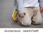 A  small toddler peeing on his pants on the street - Bed-wetting concept. Child pee on clothes.
