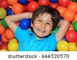 happy child lying in a balls... | Shutterstock . vector #666520570