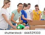 young volunteers with boxes of... | Shutterstock . vector #666529333