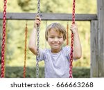 blond boy playing on a children ... | Shutterstock . vector #666663268
