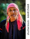 Small photo of Feb-01, 2016 : Chiang Mai, Thailand. Portrait of Akha Tribe elderly smoking tobacco pipe in the morning light