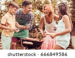happy young family barbecuing... | Shutterstock . vector #666849586