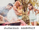 happy young family barbecuing... | Shutterstock . vector #666849619