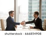 Small photo of Two happy satisfied businessmen shaking hands over desk after successful negotiations, closing sealing deal, big window city building at background, smiling partners binding agreement with handshake