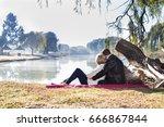 couple sitting on red blanket... | Shutterstock . vector #666867844