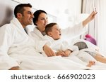 Stock photo people family and technology concept happy mother father and little boy in bathrobe taking 666902023