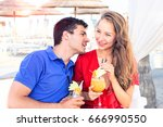 happy couple drinking cocktails ... | Shutterstock . vector #666990550