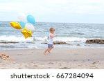 Boy Running On A Beach Holding...