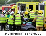 Small photo of Beaulieu, Hampshire, UK - May 29 2017: Firemen and paramedics removing the casualty from a car with a spineboard during a vehicle rescue demonstration by the UK Fire Brigade