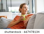 cheerful woman relaxing in sofa ... | Shutterstock . vector #667478134