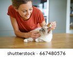 Stock photo woman injecting cat product to prevent from fleas 667480576