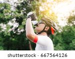 Asian Cyclist Drinking Water