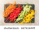 Vegan food, diet. Vegetable noodles, pasta from carrot, zucchini, bell pepper. On a black slate board on a stone table. Top view  copy space