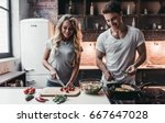 attractive couple is cooking on ... | Shutterstock . vector #667647028