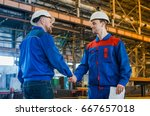 Small photo of Handshake of two men of engineers in white helmets and protective overalls against the background of a metallurgical plant. Completion of the transaction. conclusion of a contract. Conclusion