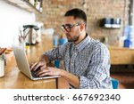 serious man working on laptop.... | Shutterstock . vector #667692340