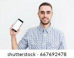 happy man showing smartphone on ... | Shutterstock . vector #667692478