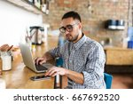 man working on laptop and using ... | Shutterstock . vector #667692520