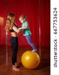 Small photo of A trainer and a little girl are engaged in a fitball. Balance and dexterity