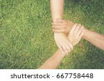 Small photo of Authentic of partnership. Close up hands together of Team Businessman agreement who is partners over green grasses background to unified powerful.Trust business in authentic of people. Trust concept.