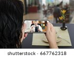 woman looks at mobile phone... | Shutterstock . vector #667762318
