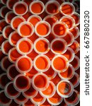 Small photo of top view of sun lit fresh dipping chili sauce in disposable plastic white saucers stacked on each other at a local street food hawker center selling home made yong tau fu in ipoh