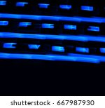 Small photo of Fuzzy motion blur of computer keyboard alphanumeric keys with dark blue neon backlight isolated on black background.