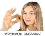 woman holding a golden bitcoin. ... | Shutterstock . vector #668000500