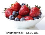 Strawberries and blueberries fill a small white bowl.  Luscious fresh berry fruit. - stock photo