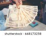 hand hold a 10000 japanese... | Shutterstock . vector #668173258