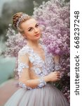 Small photo of Beautiful Romantic Girl in fairy long lacy dress standing near pink peonies .Gorgeous young model with perfect hair style and wreath accessories looking at camera in spring garden.Arr work