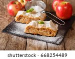 Small photo of Traditional piece of apple strudel with powdered sugar and mint closeup on a table. horizontal