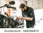 motorcycle mechanic repairing... | Shutterstock . vector #668286874