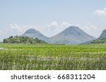 bush and mountains in lake...   Shutterstock . vector #668311204