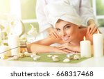 girl lying down on a massage bed | Shutterstock . vector #668317468