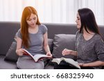 womans reading a book together... | Shutterstock . vector #668325940