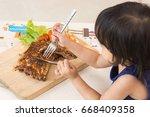little girl eating gourmet... | Shutterstock . vector #668409358