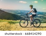 young woman riding on mtb in...   Shutterstock . vector #668414290